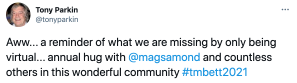 "a tweet that says ""Aww... a reminder of what we are missing by only being virtual... annual hug with mags amond and countless others in this wonderful community teachmeet bett 2021"""